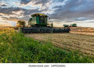 Swift Current, SK/Canada- Aug 25, 2019: Sunburst over combines and grain cart during harvest in Saskatchewan