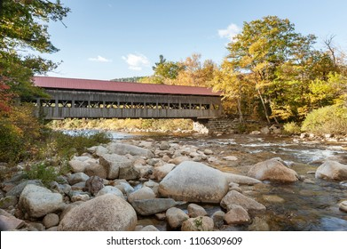 Swift River flowing past Albany Covered Bridge on sunny autumn morning
