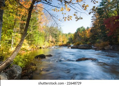 Swift river running across a colorful fall forest