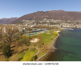 swim bay beach at Lago Maggiore close to Ascona Locarno Ticino. CH Switzerland. Drone aerial shot, early spring, very calm water, little snow on mountains in background. 27th March 2016