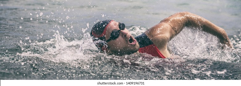 Swim triathlete man swimming freestyle crawl in ocean panorama banner. Male triathlon swimmer swimming in professional triathlon suit training for ironman on Hawaii.