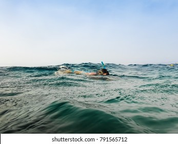 Swimmer above clear blue water while snorkeling