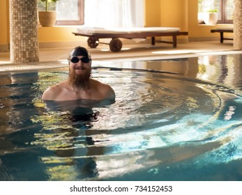 A swimmer with a beard, wearing glasses and a cap for swimming in the pool