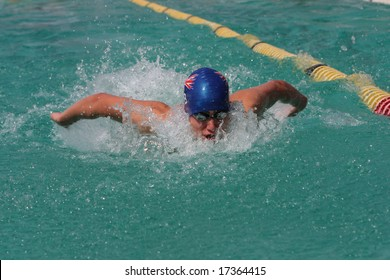 Swimmer doing butterfly stroke with face out of water and arms behind back