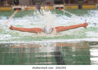 Swimmer face down doing butterfly stroke at swim event