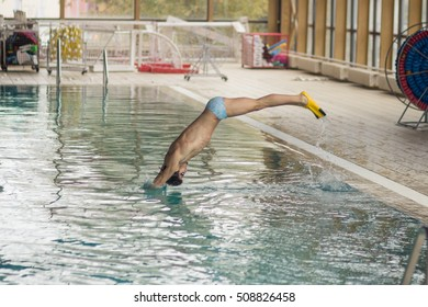 swimmer jumping in swimming pool water indoors.