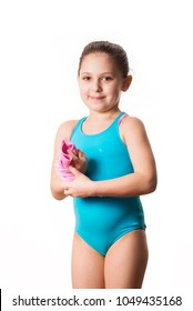 Swimmer: little 7 years old cute caucasian girlie in cyan swimming costume holding pink shammy, a chamois towel for divers. White background, copy space. Sport and ricreation concept