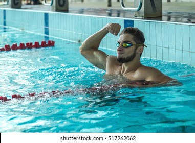 Swimmer man. Happiness swimming athlete in goggles after distance in waterpool.