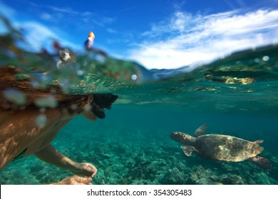 A swimmer in open water meeting sea turtle. Image with water line. Tropical snorkeling at Maldives