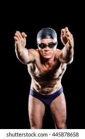 Swimmer preparing to dive on black background