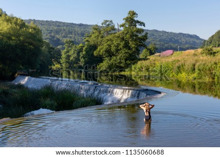 A swimmer standing in the shallows preparing to swim in the River Avon at Warleigh Weir in Somerset, England