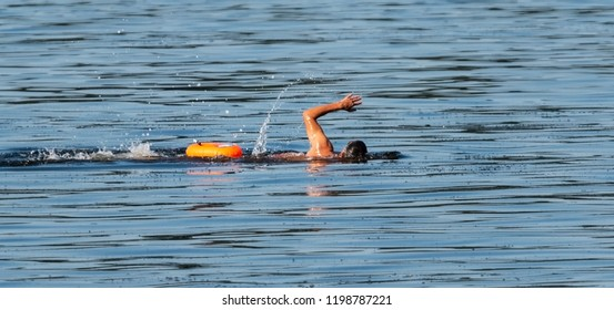 Swimmer swimming in a bay of water with an small orange floatation device strapped to waist for safety.