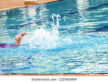 The swimmer's foot is kicking the water in the swimming pool.