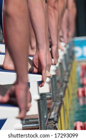 Swimmers on starting block ready to dive, waiting for the starter to give the signal