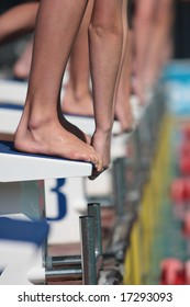 Swimmers on starting blocks ready to dive into water with only hands and feet showing