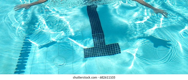 Swimming in blue water of a pool