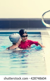 Swimming class, child with instructor, indoor pool, toned image