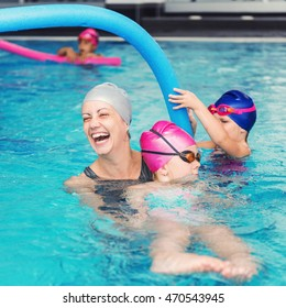 Swimming class for little children - kids having fun with swimming instructor