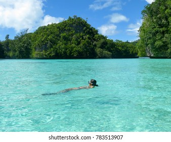 Swimming in a clear shallow cove in the Rock Islands, Palau