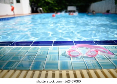Swimming goggles lying beside the pool. Children were playing in the water for fun in the summer.