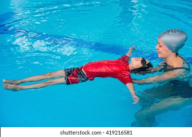Swimming lessons for children - Swimming instructor helping little boy to relax in water
