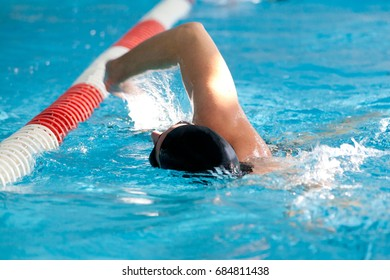 Swimming Man with black swimming cap close to floats in a row