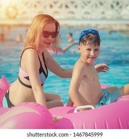 Swimming with pink rubber floater. Mother and boy on summer vacation.
