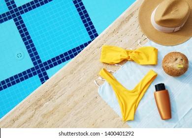 Swimming pool accessories concept. Top view of beach items on deck, bright yellow bikini bathing suit, hipster straw hat, blue mat & sunscreen skincare cream. Colorful beach wear. Flat lay, copy space