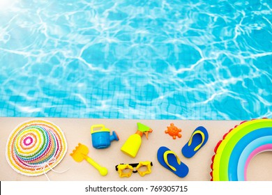 Swimming pool accessories for kids flat lay. Top view of children beach items on pool deck. Baby flip flops, hat, sun glasses and sunscreen. Water toys. Family summer vacation in tropical resort.