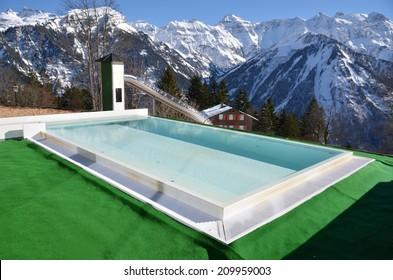Swimming pool against snowy Alps. Switzerland