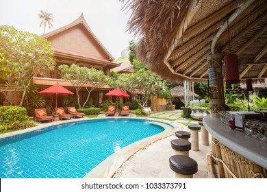 Swimming pool area with bar in luxury hotel resort. Hot summer day, holiday and travel in asia