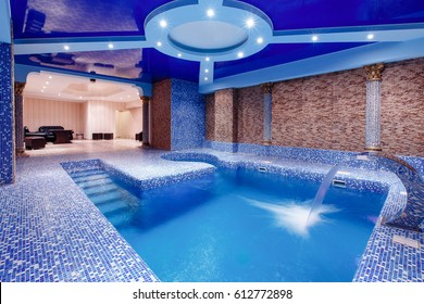 Swimming pool with blue water with a backlight and a waterfall, dark background, entrance to the sauna, the concept of hardening of health, walrus. Light in the jacuzzi.