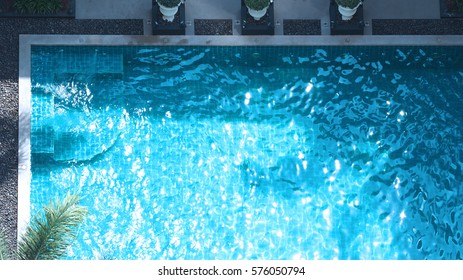Swimming pool blue water in summer and white beach beds and top view angle.