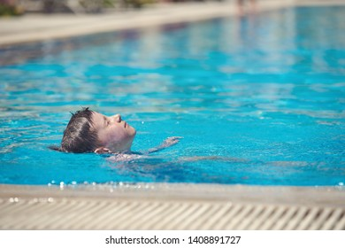 Swimming in pool. Boy is laying with his face up while swimming backstroke.