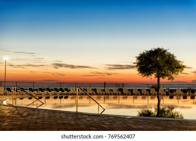 A swimming pool by the beach during sunset