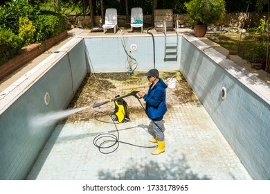 Swimming Pool Cleaning. Dirty pool, A service man is cleaning the pool ground with a pressure pump