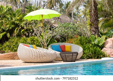 Swimming pool, coconuts palm trees, rattan daybeds and umbrella in a tropical garden near sea, Thailand