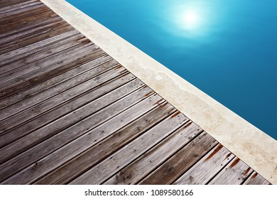 Swimming pool and the composite wooden flooring of its deck. Minimalist close up view. Concept of sun and summer holiday.