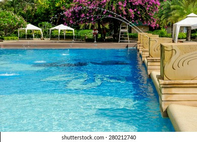 Swimming pool decorated with a fountain.