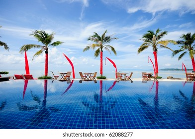 Swimming pool facing the lagoon in a tropical hotel , with coconut & beach , Samui, Thailand