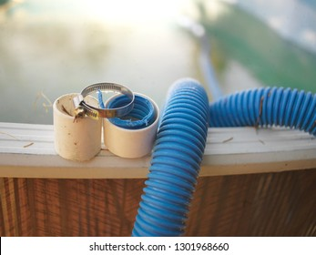 Swimming pool hose needs repair and hose clamp, outdoor close-up