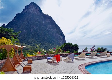 Swimming pool, lounges with bright beach towels, and shaded swings on stone deck lined with tropical flowers overlooking St. Lucia island's Petit Piton and the Caribbean sea against a cloudy blue sky.