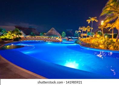 Swimming pool at a luxury caribbean resort at night, dawn time. Bahia Principe, Riviera Maya, Mexican Resort.