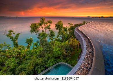 Swimming pool at luxury villa with a view of mountain and sea at beautiful sunset in Phuket, Thailand