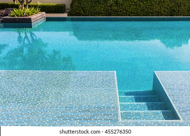 Swimming pool made by mosaic tiles with small stairs inside the clear blue water which not moving. Water surface reflects shadow of sky, tree and bush in far background.