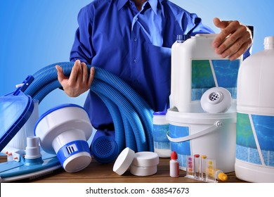 Swimming pool maintenance worker with chemical cleaning products and tools on wood table and blue background. Horizontal composition. Front view