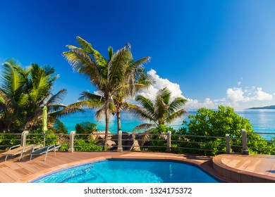 Swimming pool near tropical beach Anse Patates with palm trees on La Digue Island, Seychelles