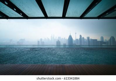 Swimming pool on roof top with beautiful city skyline view,raining day , kuala lumpur malaysia.
