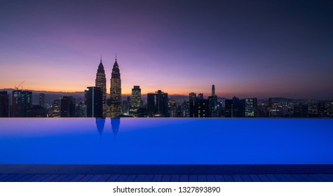 Swimming pool on rooftop with Kuala Lumpur downtown view and blue sky. Malaysia travel trip in vacation and holidays concept in Asia. Skyscraper and high-rise buildings at sunrise.