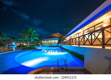 Swimming pool at promenade and restaurant at luxury caribbean resort at night, dawn time. Mexico.